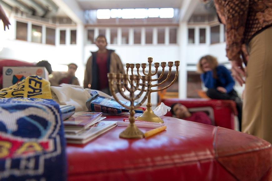 Ausstellungswürfel mit Kerzenleuchter, Büchern und Gebetsmantel darauf