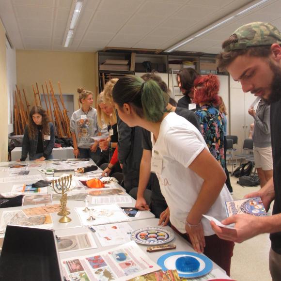 Jugendliche vor einem Tisch mit Hands-on-Objekten