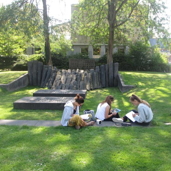 Jugendliche im Park auf einer Wiese mit Schreibutensilien