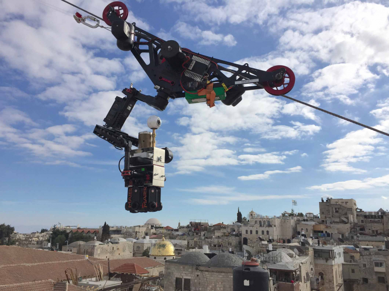 A camera mounted on a steel cable hovers before a blue sky over the rooftops of Jerusalem.