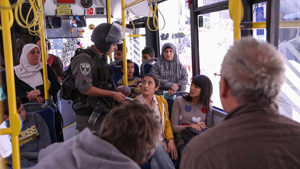An armed soldier checks civilians' identification on a bus