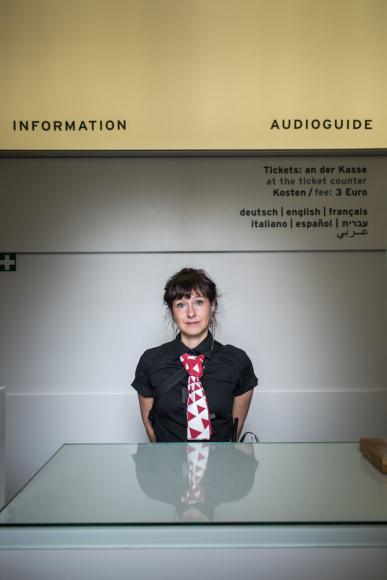 Eine junge Frau steht am Infopoint des Jüdischen Museums Berlin
