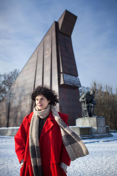 Photo: a woman in a red coat in front of the Soviet War Memorial in Treptower Park in the snow