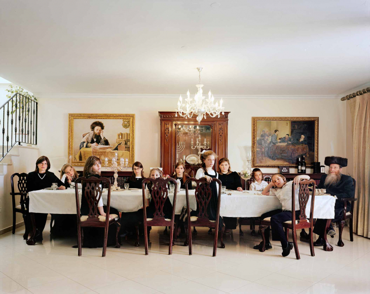 Photo of two adults and nine children around a large dining table in a representative living room with chandelier and paintings on the wall