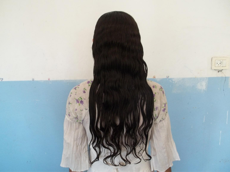 Photo of a woman from behind, from head to hip, with long dark hair in front of a blue-white wall