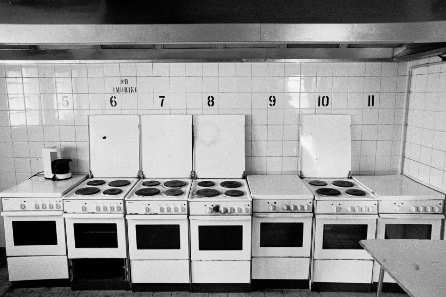 "A black and white photograph of a row of small white ovens, some of the ovens have their stovetop open, all the ovens have a black number on the wall above them next to a ""No Smoking"" sign"