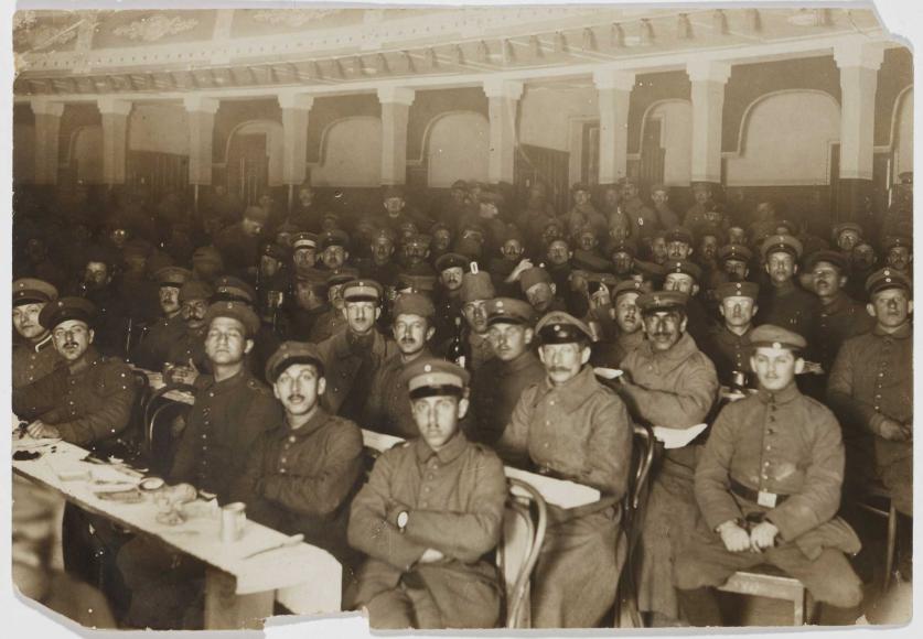 Soldaten sitzen uniformiert mit bedeckten Köpfen an langen Reihen improvisierter Tische; der vorderste ist gedeckt. Die Aufnahme wurde von einem Standpunkt rechts neben den Bankreihen aufgenommen.