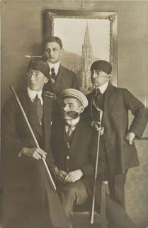 Schwarz-Weiss-Foto von vier Verbindungsstudenten vor einem großformatigen Foto des Freiburger Münsters
