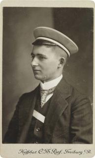 Porträtaufnahme von Erich Hirschberg als Student im Halbprofil im schwarzem Anzug mit Fuchsenband und Mütze seiner Verbindung