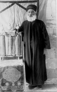Black-and-white photo of a man with a beard holding his hand above a Torah scroll