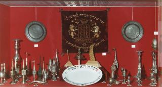 Foto einer Ausstellungsvitrine mit Judaica-Objekten vor rotem Hintergrund