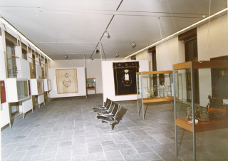 View of an exhibition hall with vitrines and seats