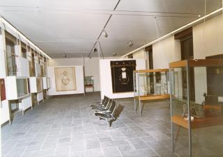 Blick in einen Ausstellungsraum mit Vitrinen und Sitzgelegenheiten