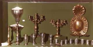 Foto einer Ausstellungsvitrine mit Judaica-Objekten vor grünem Hintergrund