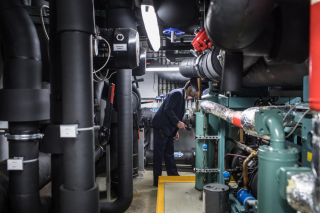 A security guard checking a room full of pipes and cables.