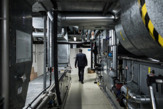 A security guard walking along a basement corridor