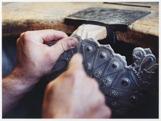 Nahaufnahme zweier Hände, die Ecken und Überschüsse eines Details der Chanukka-Lampe feilen