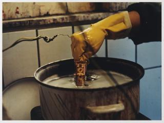 Eine Hand mit Handschuh taucht eine einzelne Dekorierung der Chanukka-Lampe in die Vergoldung