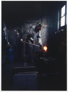 Ein Mann gießt heißes Silber in den Hohlraum der Form der Chanukka-Lampe