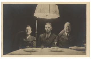 Drei Personen an einem Tisch sitzend unter einem Lampenschirm