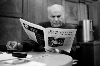 A black and white photograph of a man sitting at a table with a newspaper in his left hand and a cup in the other