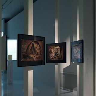 Mehrere Gemälde in einem Ausstellungsraum, die im Raum stehen und an Stelen befestigt sind