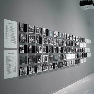 Wand mit zahlreichen Schwarz-Weiß-Fotografien, die in mehreren langen Reihen gehängt sind