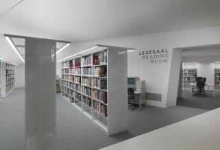 Plusieurs étagères avec des livres, en arrière-plan un bureau avec un ordinateur