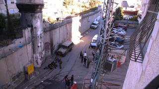 Blick von oben auf das Filmset vor der Sperrmauer mit Wachturm