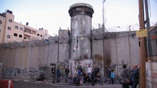 Bedrohlich wirkende Sperrmauer aus Betonfertigteilen mit Wachturm und Stacheldraht, vor der Mauer stehen und sitzen einige Menschen