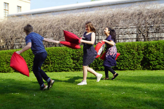 Drei Mädchen bei einer Kissenschlacht im Garten