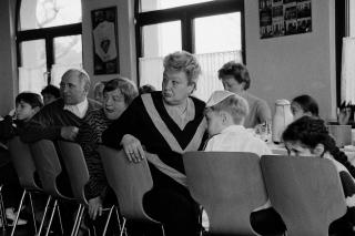 Erwachsene und Kinder sitzen an einer langen Tafel. Sie wenden sich einem Geschehen zu, das im Bild nicht zu sehen ist