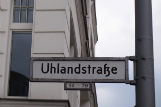 Color photo: Street sign in front of a prewar Berlin building