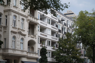 Color photo: Façades of a prewar and a postwar Berlin building, with trees