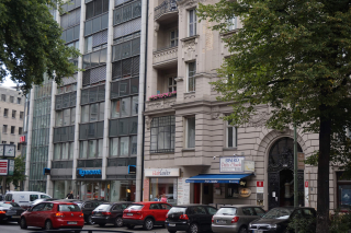 Color photo: Façades of a prewar and a postwar Berlin building, with trees and cars