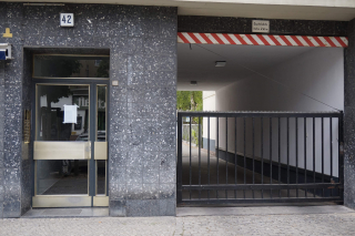 """Color photo: Glass front door with address number """"42"""" and entrance for cars"""