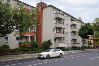 Color photo: Postwar apartment building with a taxi passing by