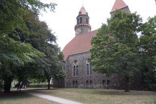 Color photo: View of the grounds of a neo-Romanesque church with two towers