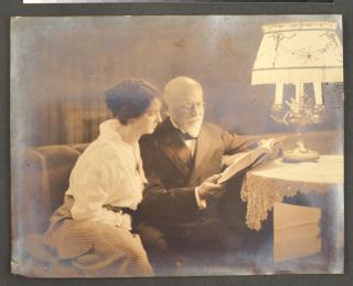 Ein älterer Herr mit seiner erwachsenen Tochter lesend unter einem Lampenschirm
