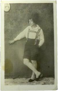 Atelierporträt einer unbekannten Frau in Ganzfigur mit Pantoffeln, heller Strumpfhose, hellem Hemd, dunkler Hose mit verzierten Hosenträgern und dunklem Hut