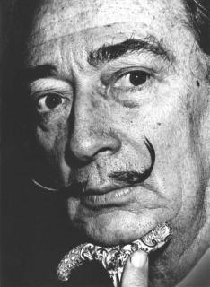 Nahaufnahme von Salvador Dalí in scharz-weiß, sein Kinn ruht auf dem Knauf eines Spazierstocks