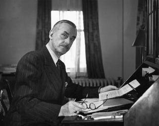 Schwarz-Weiß-Porträt von Thomas Mann, der mit Brille und Papier in den Händen an einem Sekretär sitzend in die Kamera blickt