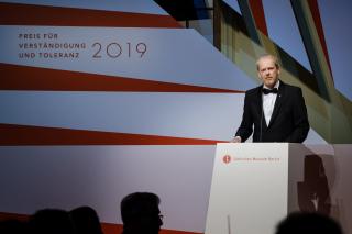 """Mann am Rednerpult neben einer Wand mit der Aufschrift """"Preis für Verständigung und Toleranz 2019"""""""