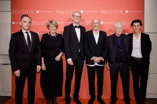 Sechs Menschen vor einer roten Wand