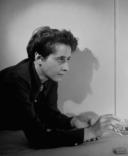 Black and white portrait of Hannah Arendt wearing a dark collar shirt leaning over an ashtray