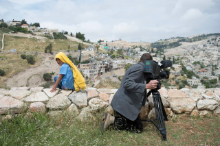 Man at movie camera and child turning over and looking into the (photo) camera, in the image background Jerusalem