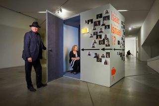A man hold the door open to a small isolated room with a smiling woman sitting inside, the outisde of the room is covered in portrait photos