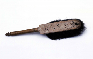 Ein Handfeger aus Holz mit stark abgenutzten schwarzen Borsten.