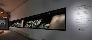 Blick auf eine lange Vitrine, in der verschiedene Publikationen ausgestellt sind, und am Ende des Raums ein Monitor