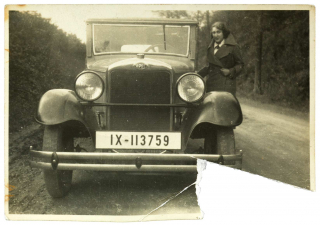 Black and white photo of a young woman in winter clothes next to a car on a country road, the lower right corner of the photograph is torn out.